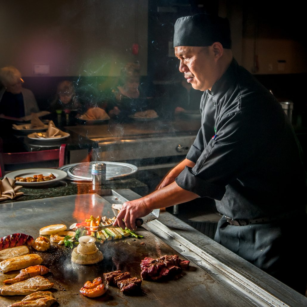 Japanese teppan yaki master chef at the grill with meat and veggies