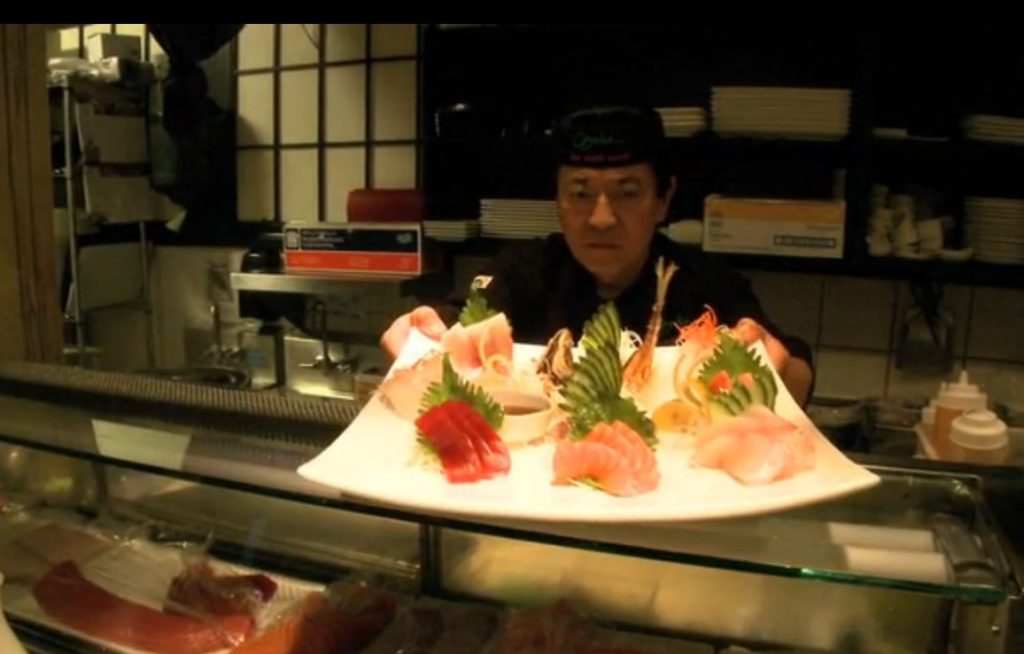 Sushi chef offering a plate of sushi over the bar at Osaka Japanese Bistro Las Vegas