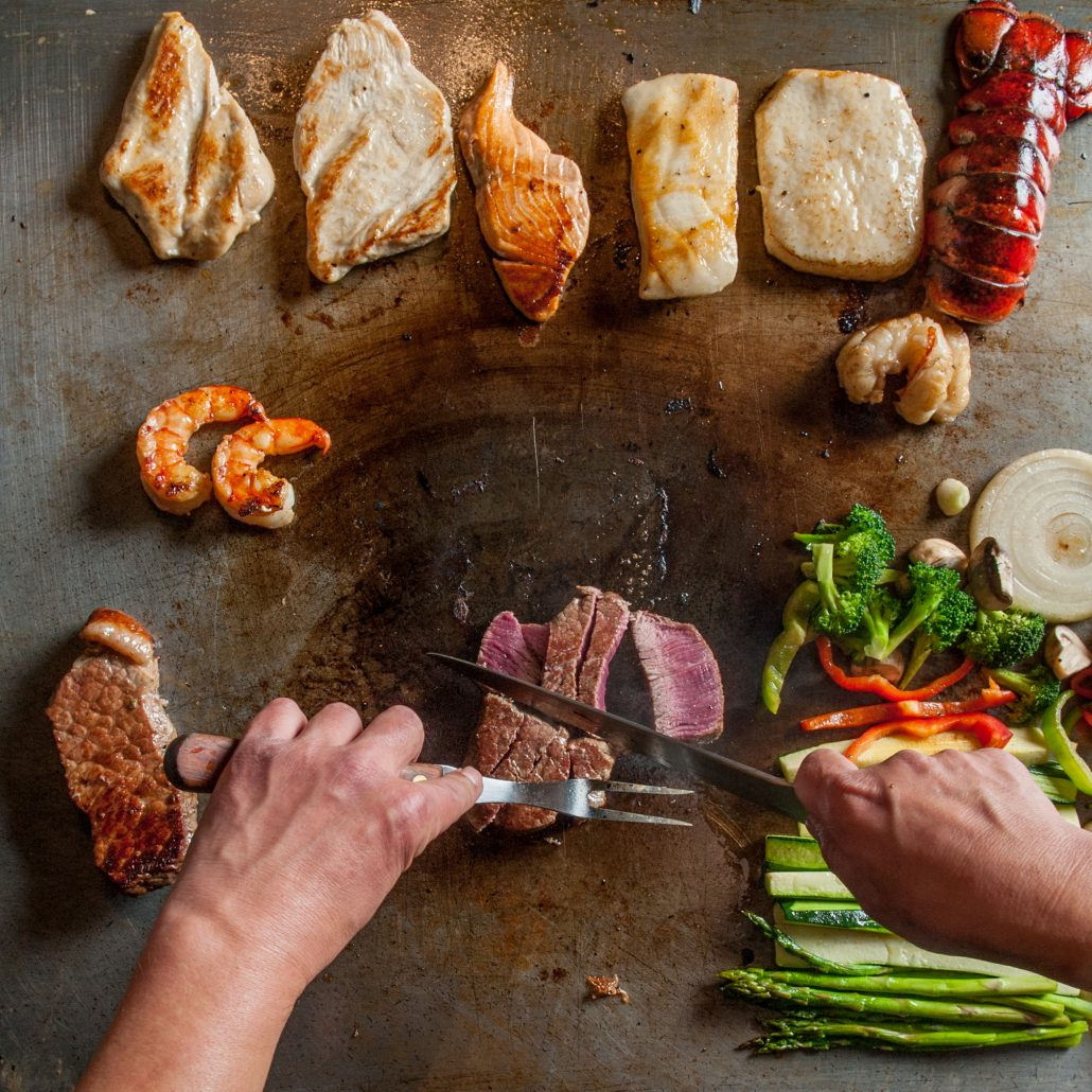 Teppan grill selection of foods on the grill beef chicken fish lobster and veggies