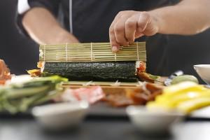 sushi master twisting sushi nori rolls on a bamboo mat
