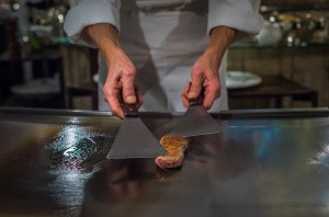 Chef cooking wagyu beef in Japanese teppanyaki restaurant