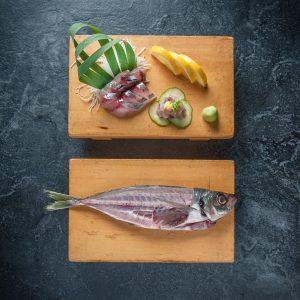 Mackarel fish sliced on sushi cutting board