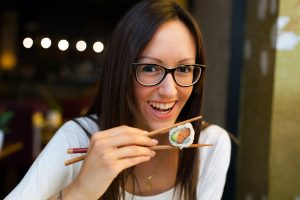 Smiling woman eating sushi with chopsticks in Japanese restaurant